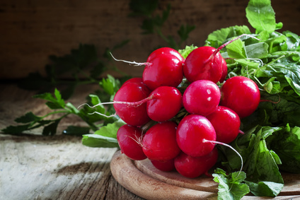 bunch of red radishes on a cutting board, selective focus